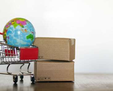 Shopping cart carton and earth globe. International shopping and global logistics concept