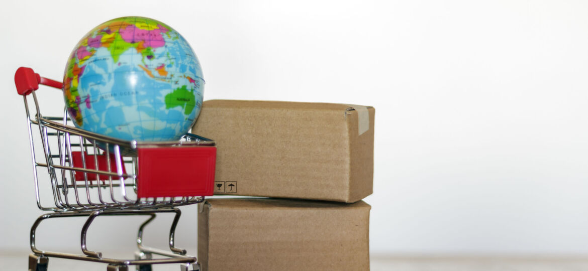Shopping cart, delivery boxes and earth globe. Worldwide shopping and global logistics concept