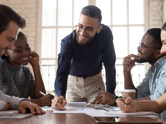 Smiling Arabic businessman hold team meeting in office